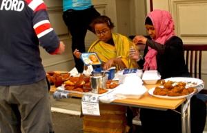 Two Somali girls serving samosa.