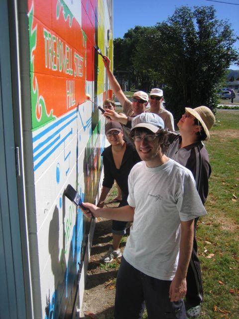 Team of volunteers painting over a mural